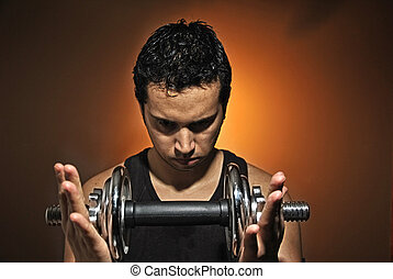 aggressive athlete training with dumbbells
