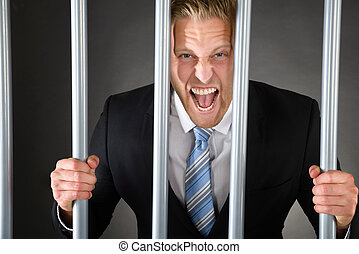 Portrait Of Aggressive Businessman Standing Behind Bars