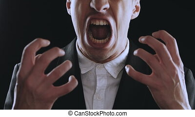 aggressive businessman in a suit is screaming and showing anger on a black background. Angry boss. The danger of violence