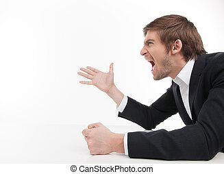 Aggressive businessman. Side view of angry young businessman shouting and gesturing while isolated on white