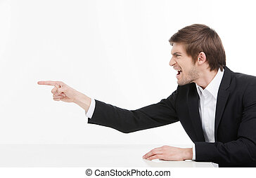 Aggressive businessman. Side view of angry young businessman shouting and pointing away while isolated on white