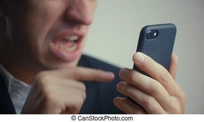 aggressive businessman uses smartphone and screams. evil...