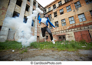 Portrait of furious dude jumping with smoking detonator tube