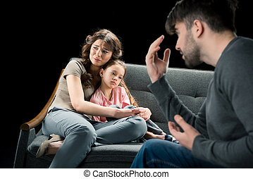 Aggressive man gesturing while crying woman hugging with daughter on couch, family problems concept