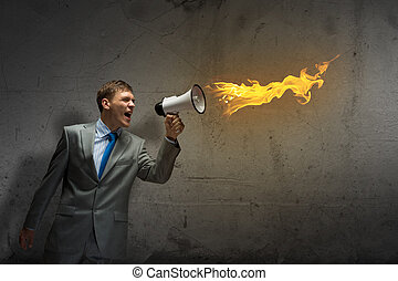 Young aggressive businessman screaming furiously in megaphone