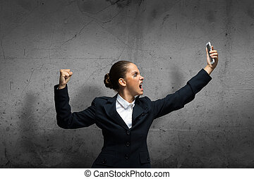 Young aggressive businesswoman screaming in mobile phone