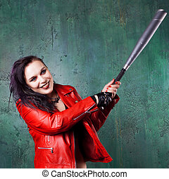 Aggressive punk woman strike someone with a bat, in red leather jacket