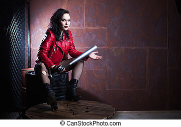 Aggressive punk woman with a bat, in red leather jacket