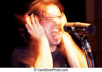 An aggressive music singer recording in a studio. Lots of mood and atmosphere created with timed exposure with hand-held flash. (some film grain because of the 1600 ISO film used)