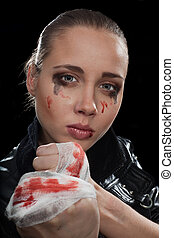 Young aggressive woman with fist and blood on her