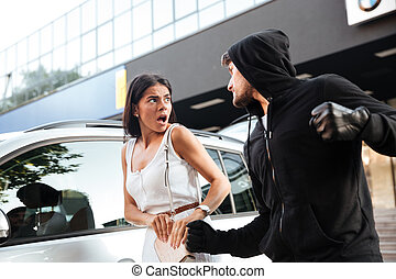 Aggressive young man thief in hoodie robbing scared woman -...