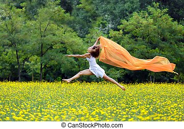 Agile woman leaping in the air trailing a scarf