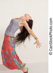 Agile young woman arching her back with her arms...