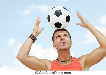 Agility - Portrait of a muscular man with football ball on...