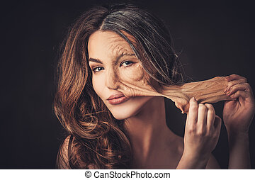 Aging and skin care concept. Half old half young woman,...