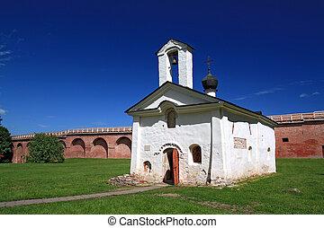aging blanching church amongst green herb
