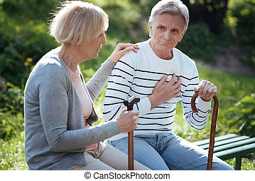 Aging couple sitting and feeling bad in the park