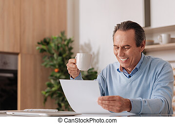 Aging delightful freelancer working at home