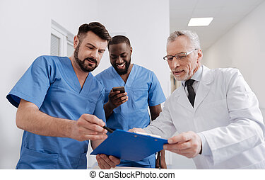 Aging friendly mentor checking the report of interns in the hospital