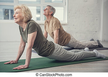 Aging people developing their flexibility - Pleased mature ...