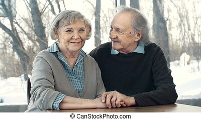 Aging Together - Close up of jolly senior couple sitting at...