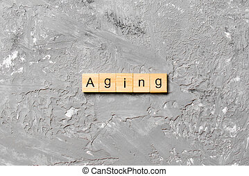 Aging word written on wood block. Aging text on cement table for your desing, concept