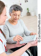 agradável, mulher idosa, fazendo exame pills