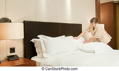 Agreeable chambermaid making bed in hotel room
