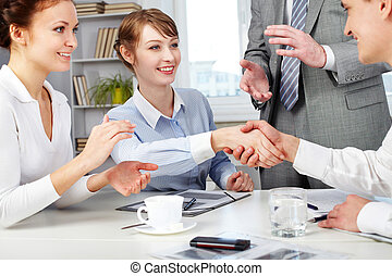 Image of business partners making an agreement with woman clapping her hands near by