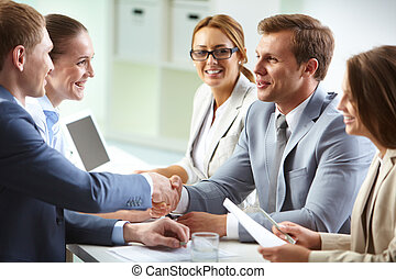 Agreement - Image of confident businessmen handshaking at ...