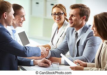 Agreement - Image of confident businessmen handshaking at ...