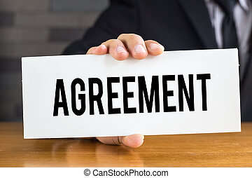 Agreement, message on white card and hold by businessman