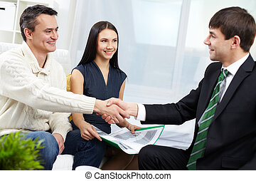 Agreement - Portrait of modern couple making a deal with...