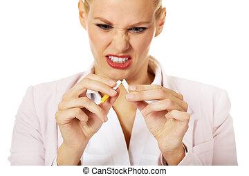 Agressive business woman breaking cigarette