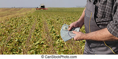 Agricultural concept, farmer, money and soybean field harvest