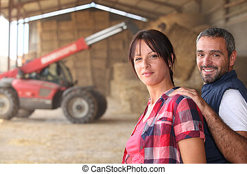 Agricultural couple in the barn with a tractor