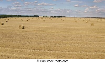 Dry rural field with hay stacks, drone flying over aerial