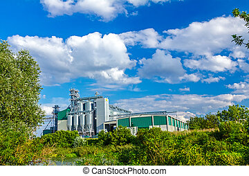 Processing plant for prodicing sunflower oil against blue sky.