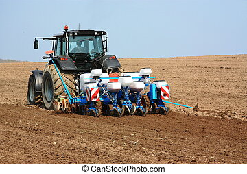 Agricultural Planter - A tractor towing a planting and...