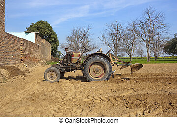 punjabi agricultural landscape with a cattle egret beneath a tractor equipped to prepare for planting okra in a cultivated field