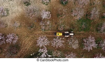 drone image of people doing agricultural spraying with tractor