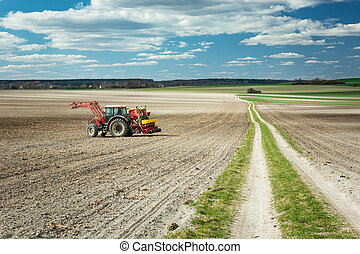 Agricultural tractor in a plowed field, long dirt road and clouds on a blue sky