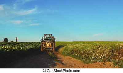 Agricultural tractor in cultivated field, crane shoot. -...