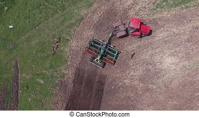 Agricultural tractor sowing seeds and cultivating field....