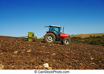 agricultural tractor sowing seeds and cultivating field
