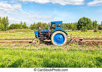 Agricultural tractor working at the potato field