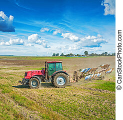 Agricultural view tractor with plough standing on field