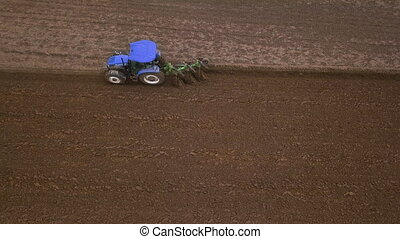 Agricultural work in the field, two blue tractors plow the ...
