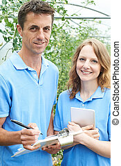 Agricultural Workers Checking Tomato Plants Using Digital Tablet