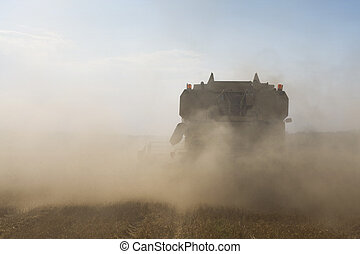 Agriculture - Combine in cloud of impurity during harvesting